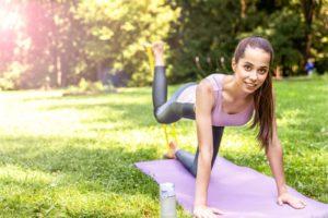 Junge Frau lächelnd bei klassischer Yogaübung